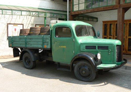 Staré nákladní auto s naloženými dřevěnými sudy
